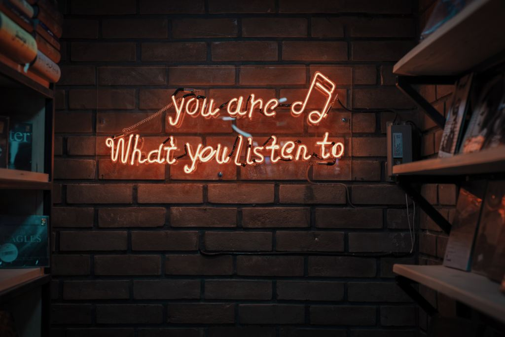"""Neon sign reading """"You are what you listen to""""."""